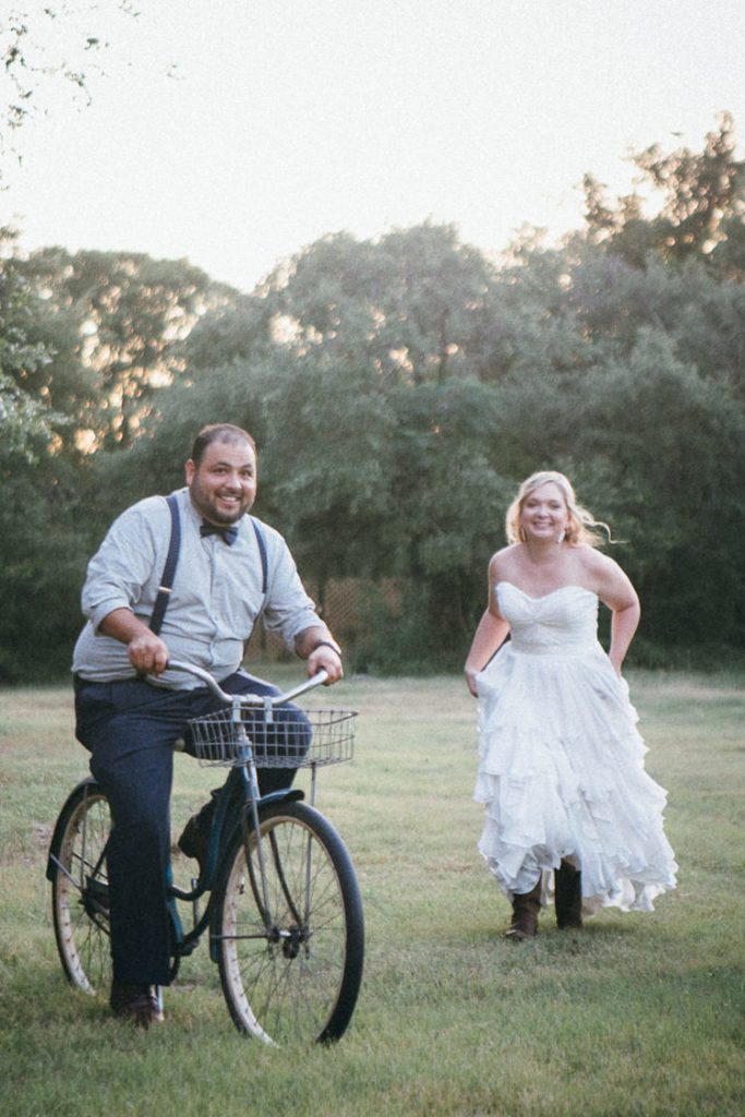 groom riding vintage schwinn with bride chasing