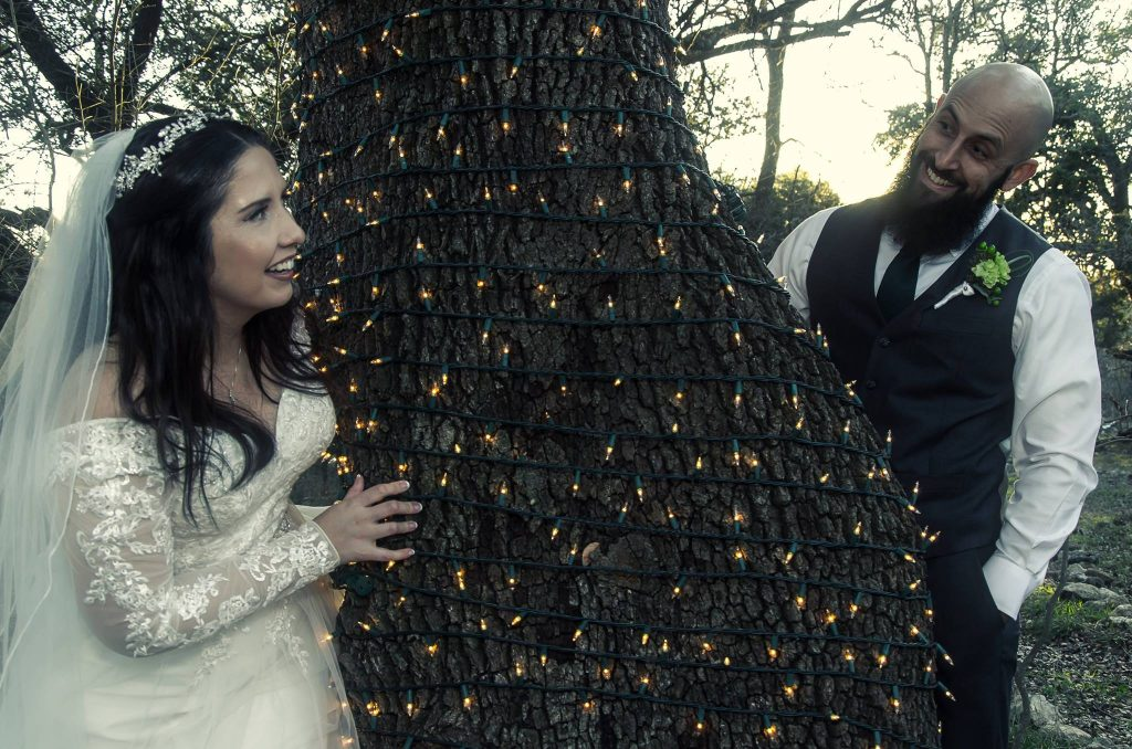 Bride and groom peek around oak tree