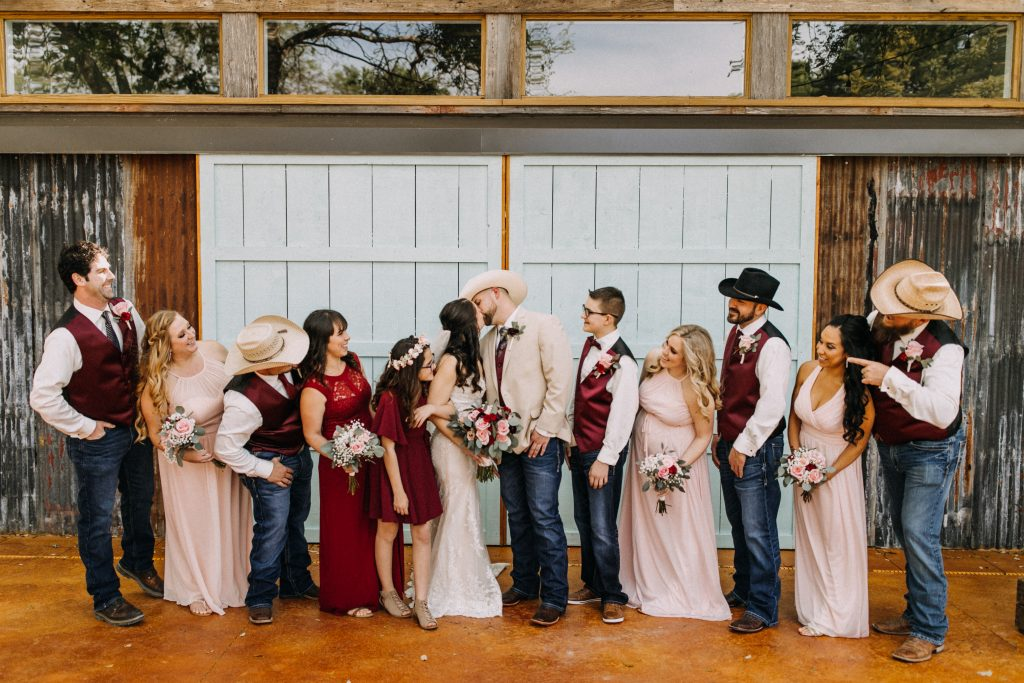 Bridal party and couple kiss Temple texass wedding