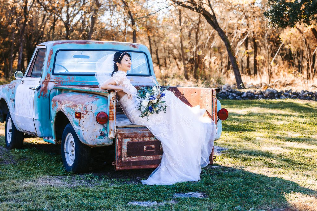 bride sitting in back of old truck