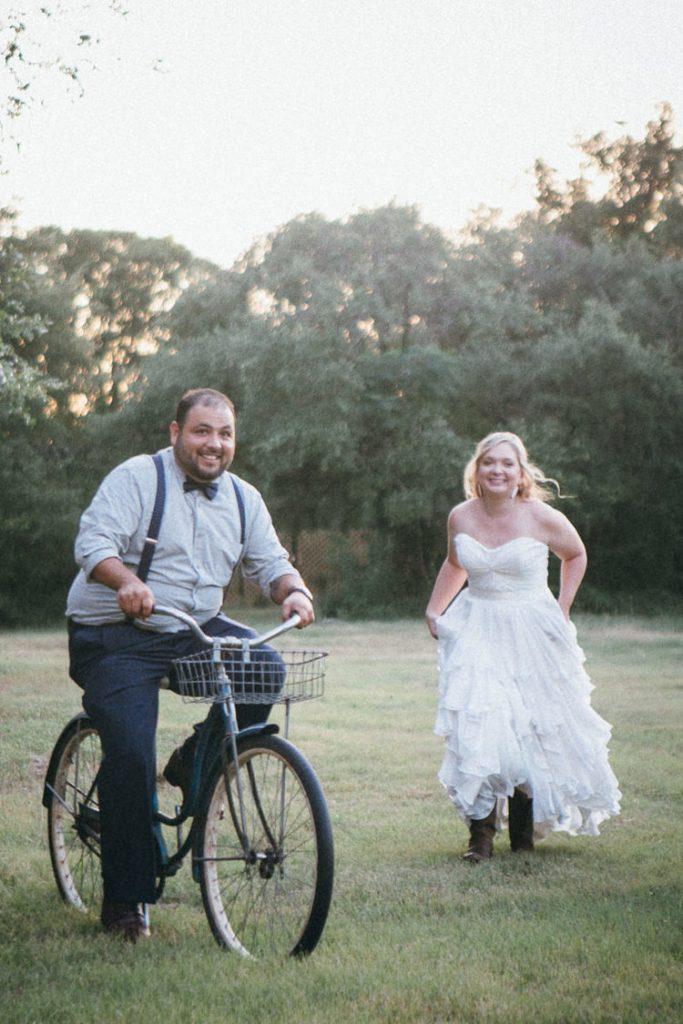 groom riding vintage schwinn with bride chasing