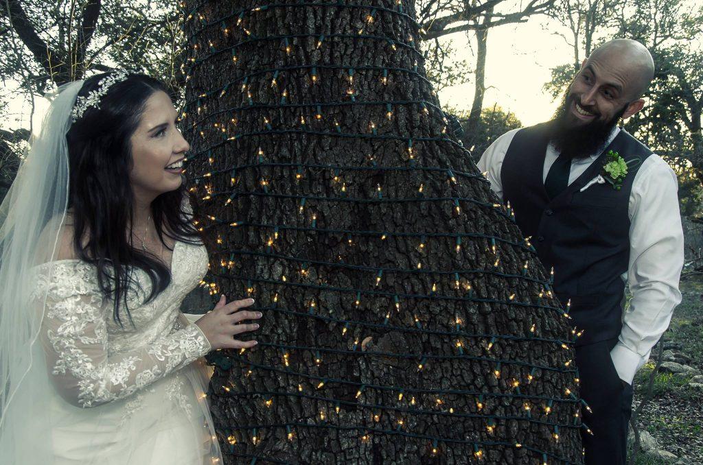 Bride and groom peek around oak tree