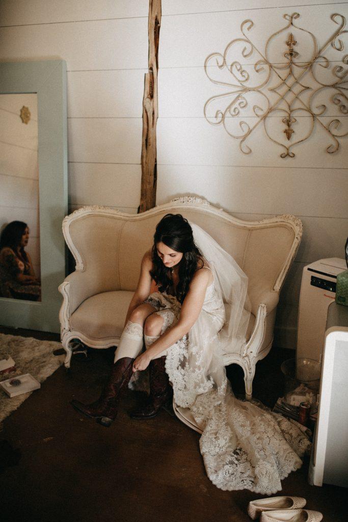 Bride putting boots on in bride's suite Temple Texas Venue