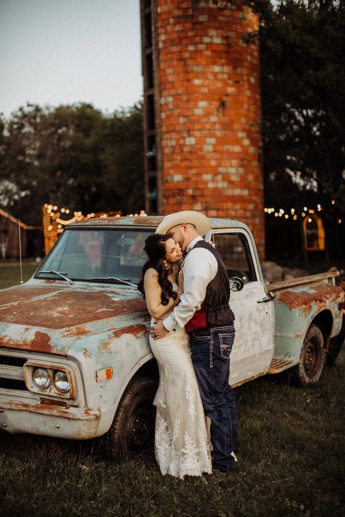 Couple and old truck by the Silo Temple Texas Wedding Venue