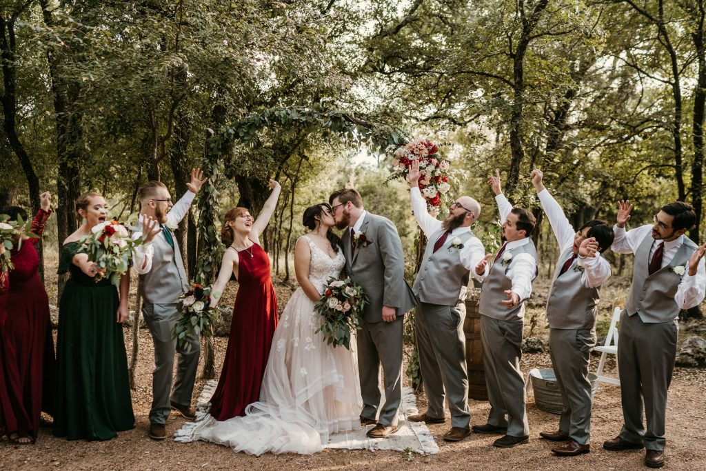 bridal party with couple at arch