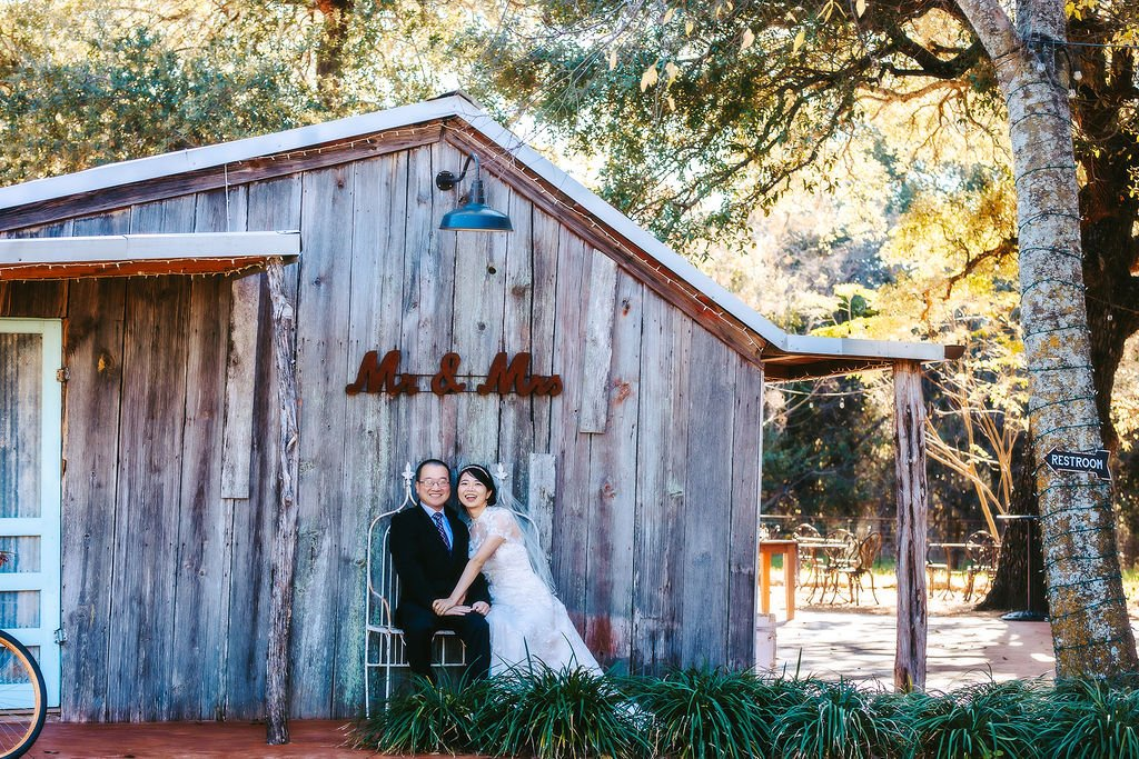couple sitting under mr and mrs sign